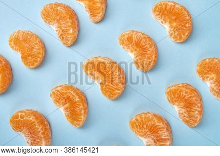 Rows Of Mandarin Slices. Mandarin Parts Arranged In Rows Isolated On Blue Background.