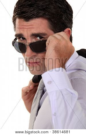 Businessman peering over his sunglasses