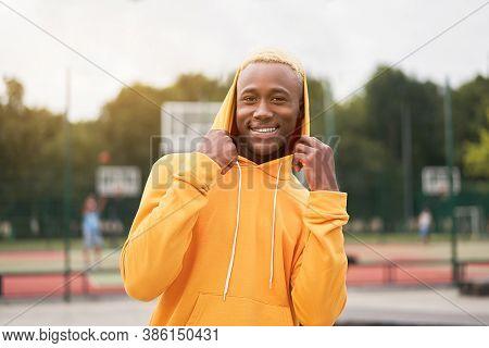 African-american Smiling Black Man Wearing Hood On Head Dressed Yellow Hoodie Outside Happy Emotiona