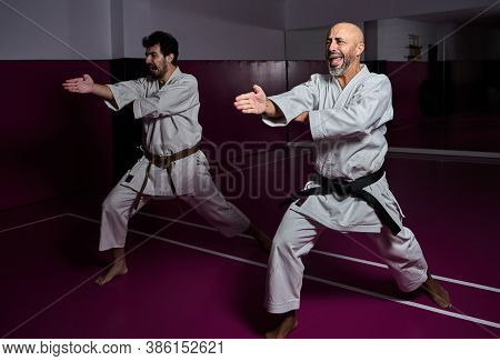 Karate Master And His Apprentice Practicing Martial Arts Attack In Their Dojo
