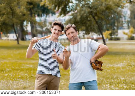 Teenager Son With Softball Bat Showing Thumb Up Near Father In Leather Glove Holding Ball