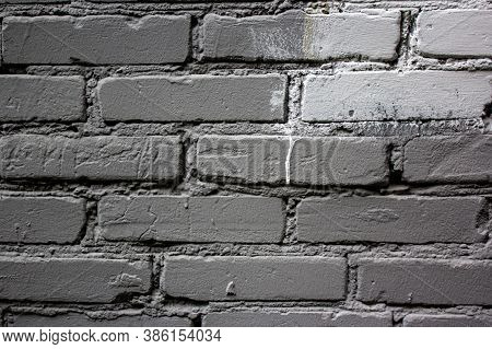 Old Wall Made Of Grey Brick, Painted Grey In Loft Style. A Spot Of White Paint On A Gray Brick Wall.