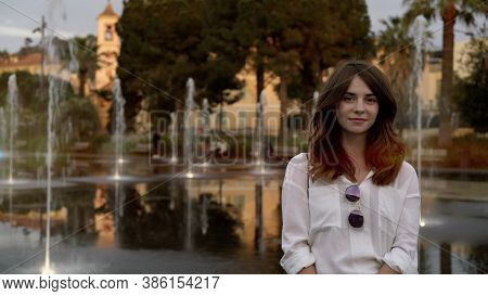 Young Beautiful Woman On Background Of Fountain In Nice, Summer In French City. Woman With Long Hair