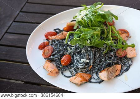 Black Spaghetti Pasta Colored With Squid Ink, Cream Sauce, Salmon, Tomatoes And Rocket Salad In A Wh