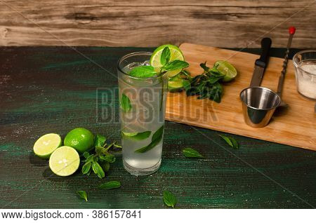 Mojito, Cocktail Of Cuban Origin, On A Green Table Decorated With Cocktail Ingredients. Wooden Backg