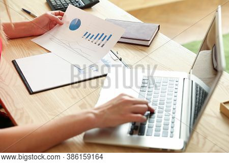 Business Analytics Concept. Hands Of Businesswoman Are Typing On Laptop And Analyzing Paper Charts.