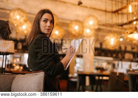 Business Young Woman Wearing Stylish Formal Clothes In Modern Luxury Restaurant Holding Paper Docume