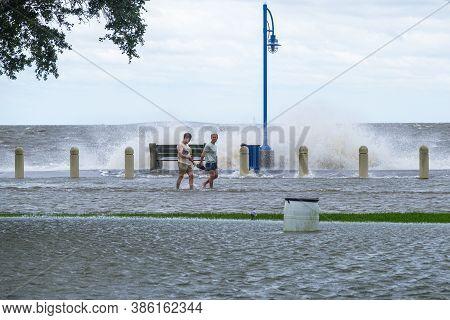 New Orleans, Louisiana/usa - 9/15/2020: Two Men Walking Along Flooded Lakeshore Drive And Lake Pontc