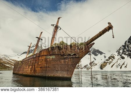 An Abandoned Ship In Antarctica, Abandoned Ship At The North Pole With Ice Mountains In The Backgrou