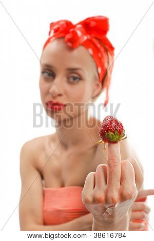 Sexy young woman is showing fuck off with the middle finger with picked red strawberry. Focus on hand. Isolated on white background