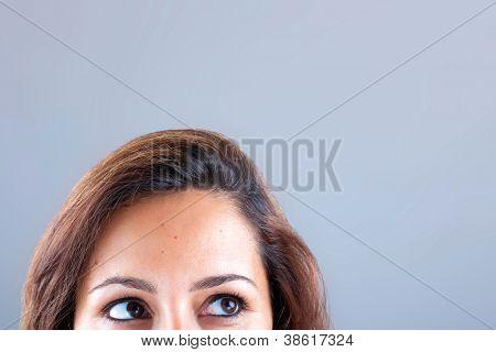 Closeup Portrait einer jungen Frau, die auf grauen Hintergrund nachschlagen