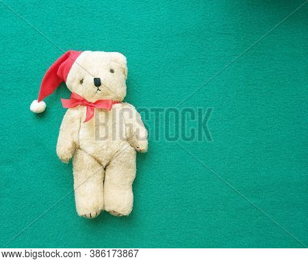 Toy Polar Bear In A Red Santa Claus Hat With A Bow On A Green Background. Christmas Banner. Copy Spa