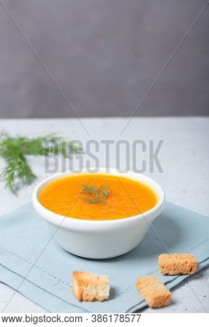 Pumpkin Soup In A Bowl With Fresh Dill Herb