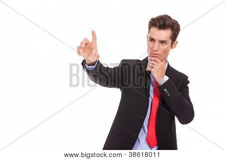 Young business man pushing imaginary digital buttons. Cool serious businss man