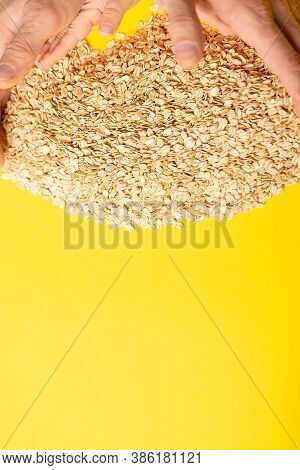 Uncooked Healthy Oat Flakes On Yellow Background