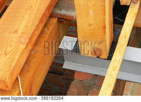 A Close-up On Wooden Roof Beam, Truss, Rafter Installation On A Metal Brace Using Corner Flashing.
