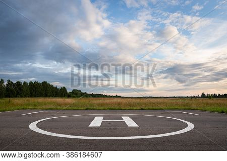 A Closeup Of An Asphalt-covered Helipad With A Special Symbol In The Center For Helicopter Landing,