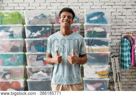 Cheerful Guy Smiling At Camera, Showing Thumbs Up, Posing In Front Of Rack And Boxes Full Of Clothes