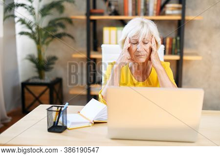 An Elderly Woman Holding Head With Hands While Sitting And Working With A Laptop Indoors. Tired From