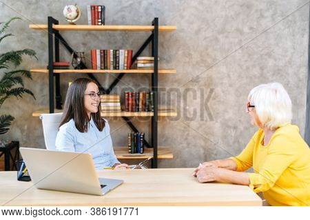Job Interview. Young Female Employee From Hr Department Is Interviewing Senior Female Applicant In T