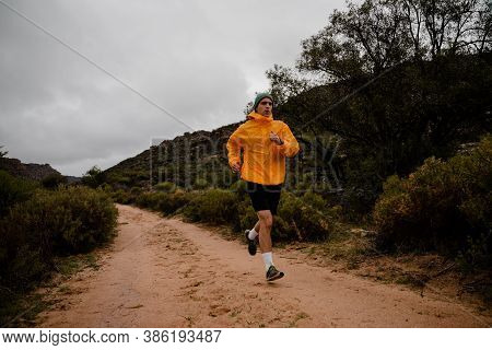 Tired Fit Young Male Runner Sweating Finishing Fast Run Down Mountain Path In Cloudy Weather With Bu