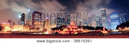 Chicago skyline panorama with skyscrapers and Buckingham fountain in Grant Park at night lit by colorful lights. poster