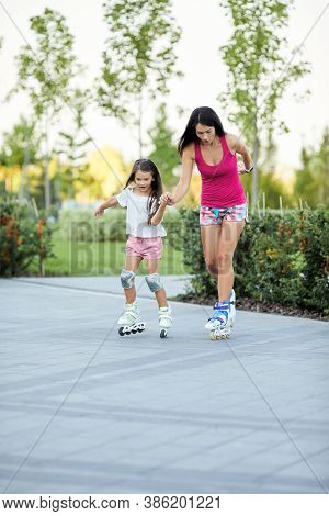 Young Mother And Her Little Daughter Rollerskating In Summer Park