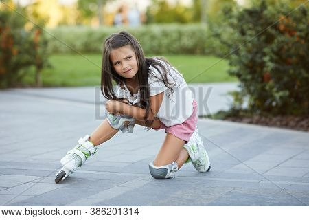 Cute Little Child Girl Falled Down While Rollerskating In Park.