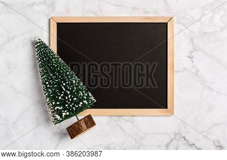 Simple Christmas Flatlay With Blank Blackboard And Fir Tree On Marble Background. Copy Space For Gre