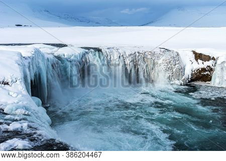 Scenic Winter View Of Godafoss Waterfall In Iceland. Picturesque Winter Landscape With Frozen Waterf