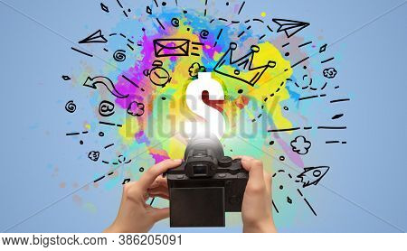Close-up of a hand holding digital camera with abstract drawing and $ inscription