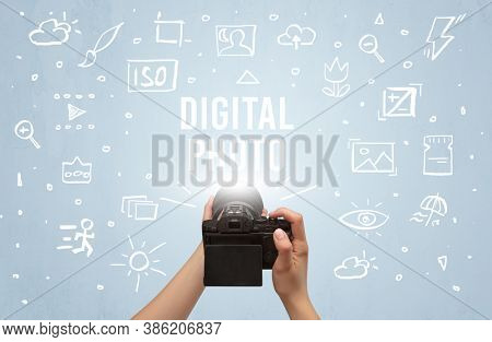 Hand taking picture with digital camera and DIGITAL PHOTO inscription, camera settings concept