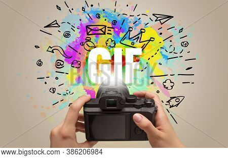Close-up of a hand holding digital camera with abstract drawing and GIF inscription
