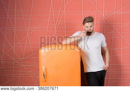 Bachelor With Morning Drink At Refrigerator. Man Hold Cup Of Tea Or Coffee In Kitchen. Macho Drink A