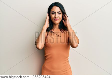 Beautiful hispanic woman wearing summer dress covering ears with fingers with annoyed expression for the noise of loud music. deaf concept.