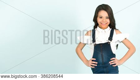 Kid Girl Smile In Fashionable Jeans Overall With Hands On Hip On Blue Background. Fashion, Beauty, S