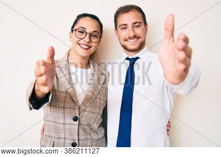 Beautiful couple wearing business clothes smiling friendly offering handshake as greeting and welcoming. successful business.