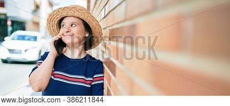 Beautiful brunette woman with down syndrome at the town on a sunny day talking on smartphone leaning on a bricks wall
