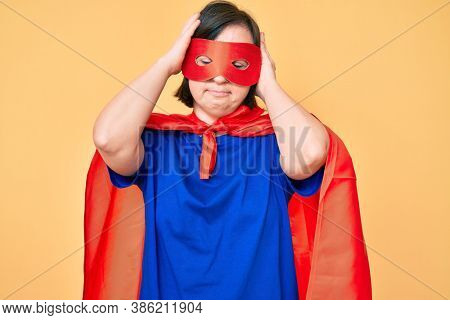 Brunette woman with down syndrome wearing super hero costume suffering from headache desperate and stressed because pain and migraine. hands on head.