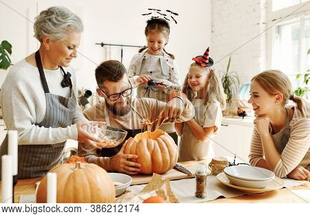 Happy Multi Generational Family Smiling And Carving Jack O Lantern From Pumpkin While Gathering Arou
