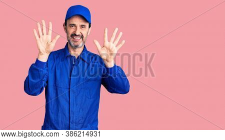 Middle age handsome man wearing mechanic uniform showing and pointing up with fingers number ten while smiling confident and happy.