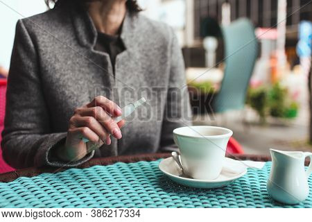 Cut View Of Business Woman Sit Alone At Cafes Table Holding Electronic Cigarette In Hand. Cup Of Tea