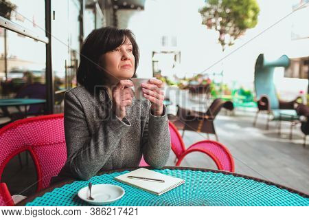 Mature Business Woman Sit Alone And Thinking. Holding White Cup Of Tea Or Coffee And Look To Side. T