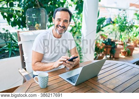 Middle age man with beard smiling happy at the terrace working from home using laptop and smartphone