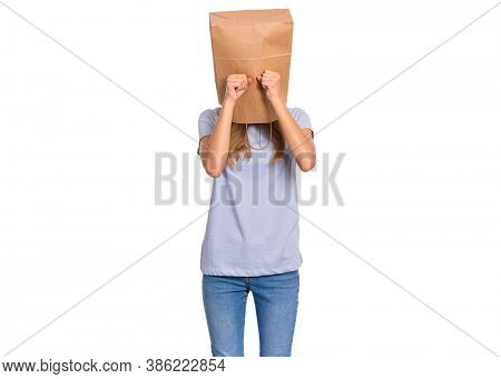 Unhappy teen girl with paper bag over head covering face with hands while crying. Upset teenager posing in studio. Child crying, not showing her tears.