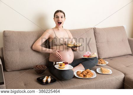 Hungry Pregnant Woman Sitting On The Sofa Is Eating A Lot Of Unhealthy Food Such As Donuts, Cakes, C