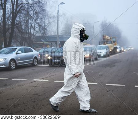Full Length Of Ecologist In Shoe Covers Walking On City Road With Cars. Male Environmentalist Wearin