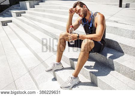 Young Man Exercising Outside. Athletist Sit Down On Steps And Resting After Workout. Holding Water B