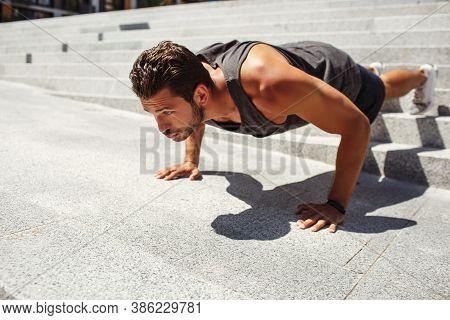 Young Man Exercising Outside. Hardworking Athlete Doing Push Up Exercise Alone At Steps Outside. Man