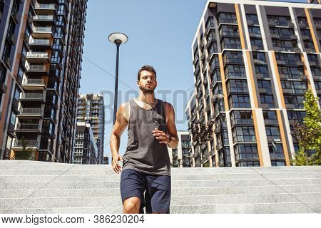 Young Man Exercising Outside. Serious Concentrated Guy Walking Down Steps Outisde On Street Alone. F